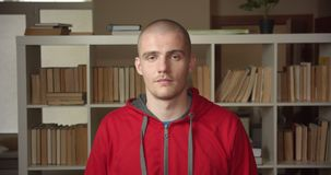 Closeup portrait of young attractive caucasian male student nodding saying yes showing agreement looking at camera in. The college library indoors stock video footage