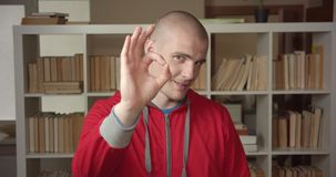 Closeup portrait of young attractive caucasian male student showing okay sign looking at camera in the college library. Indoors stock footage