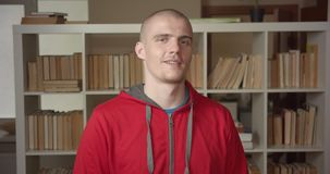 Closeup portrait of young attractive caucasian male student showing a thumb up looking at camera in the college library. Indoors stock footage