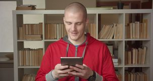 Closeup portrait of young attractive caucasian male student texting on the tablet in the college library indoors.  stock video footage