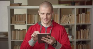 Closeup portrait of young attractive caucasian male student texting on the tablet looking at camera in the college. Library indoors stock video footage