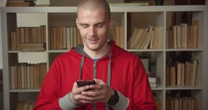 Closeup portrait of young attractive caucasian male student using the phone in the college library indoors.  stock video