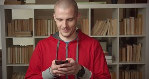 Closeup portrait of young attractive caucasian male student using the phone looking at camera and smiling in the college. Library indoors stock video