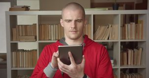 Closeup portrait of young attractive caucasian male student using the tablet and showing green chroma screen to camera. In the college library indoors stock video