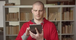 Closeup portrait of young attractive caucasian male student using the tablet and showing green screen to camera in the. College library indoors stock video
