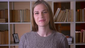 Closeup portrait of young attractive female student looking at camera and smiling happily with excitement in the college. Library indoors stock footage