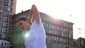 Closeup portrait of young attractive fit caucasian female stretching and preparing for workout outdoors on the stadium.  stock footage