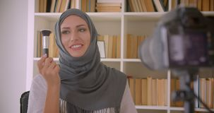 Closeup portrait of young attractive muslim beauty blogger in hijab talking on camera indoors.  stock footage