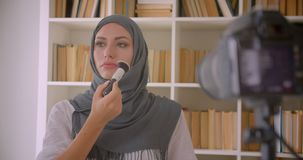 Closeup portrait of young attractive muslim beauty blogger in hijab talking on camera making makeup product review. Indoors stock footage