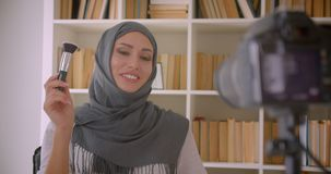 Closeup portrait of young attractive muslim beauty blogger in hijab talking on camera making product review indoors.  stock video