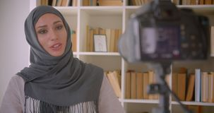 Closeup portrait of young attractive muslim blogger in hijab talking on camera gesturing indoors.  stock footage