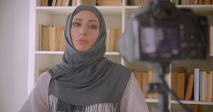 Closeup portrait of young attractive muslim blogger in hijab talking on camera gesturing indoors in apartment.  stock footage