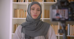 Closeup portrait of young attractive muslim blogger in hijab talking on camera indoors with bookshelves on background.  stock footage