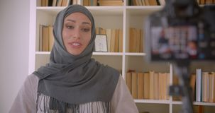 Closeup portrait of young attractive muslim blogger in hijab talking on camera laughing happily indoors with bookshelves. On background stock footage