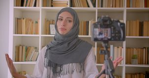 Closeup portrait of young attractive muslim blogger in hijab talking on camera smiling happily indoors.  stock footage