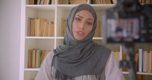 Closeup portrait of young attractive muslim blogger in hijab talking on camera streaming live indoors with bookshelves. On background stock video