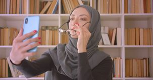 Closeup portrait of young attractive muslim businesswoman in glasses and hijab taking selfies on phone sitting in front. Of laptop in library indoors stock video footage