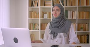 Closeup portrait of young attractive muslim businesswoman in hijab dancing sitting in front of laptop in office indoors stock video