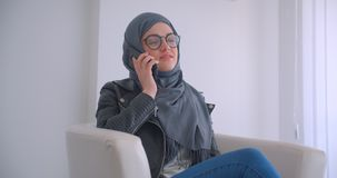 Closeup portrait of young attractive muslim businesswoman in hijab and glasses talking on the phone sitting in an. Armchair indoors in the office stock video footage