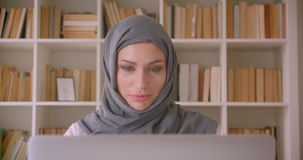 Closeup portrait of young attractive muslim businesswoman in hijab having a video call drinking coffee in library. Indoors stock footage