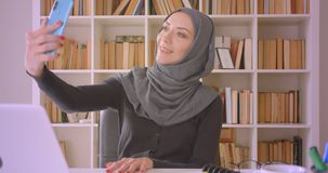 Closeup portrait of young attractive muslim businesswoman in hijab having a video call on phone sitting in front of. Laptop in library indoors stock footage