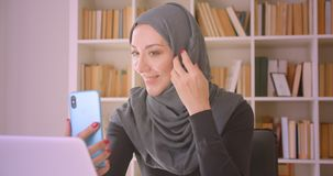 Closeup portrait of young attractive muslim businesswoman in hijab having a video call on phone talking cheerfully. Sitting in front of laptop in library stock video footage