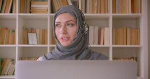 Closeup portrait of young attractive muslim businesswoman in hijab and headphones using laptop and having a call in stock video