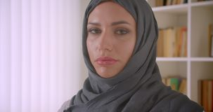 Closeup portrait of young attractive muslim businesswoman in hijab looking at camera in office indoors stock video footage