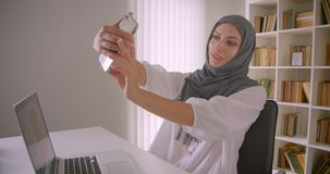 Closeup portrait of young attractive muslim businesswoman in hijab taking selfies on phone posing sitting in front of. Laptop in office indoors stock video
