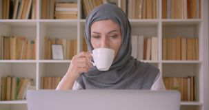 Closeup portrait of young attractive muslim businesswoman in hijab using laptop drinking coffee in library indoors stock footage