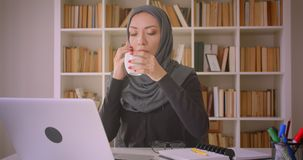 Closeup portrait of young attractive muslim businesswoman in hijab using laptop and having phone call taking notes. Drinking coffee in library indoors stock video footage