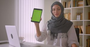 Closeup portrait of young attractive muslim businesswoman in hijab using tablet and showing green chroma screen to. Camera in office indoors stock video footage