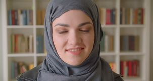 Closeup portrait of young attractive muslim female student in hijab smiling happily looking at camera in the college