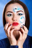 Closeup portrait of a young attractive woman with a blue face ar Stock Images