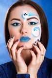 Closeup portrait of a young attractive woman with a blue face ar Stock Image