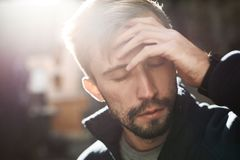 Closeup portrait of a young bearded crying man standing in backlight on the street. Closeup portrait of a young bearded crying man in warm fleece sweater. man is stock photography