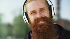 Closeup portrait of young bearded hipster man with headphones listen to music and smiling at city street stock photography