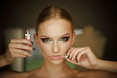 Closeup portrait of young beautiful blonde woman applying red lip gloss. royalty free stock photos