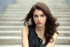 Closeup portrait of young beautiful brunette woman in black leather jacket posing outdoors against concrete stairway background Royalty Free Stock Images