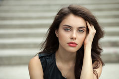 Closeup portrait of young beautiful brunette woman in black leather jacket posing outdoors against concrete stairway background Royalty Free Stock Photo