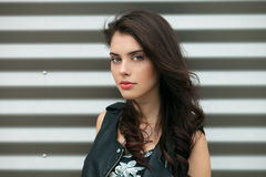Closeup portrait of young beautiful brunette woman in black leather jacket posing outdoors against urban style background of metal Royalty Free Stock Images