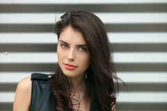 Closeup portrait of young beautiful brunette woman in black leather jacket posing outdoors against urban style background of metal. Closeup portrait of young Royalty Free Stock Photos