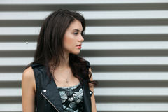 Closeup portrait of young beautiful brunette woman in black leather jacket posing outdoors against urban style background of metal. Closeup portrait of young Stock Photos