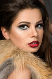 Closeup portrait of young beautiful brunette woman. With cherry lips wearing fur jacket Royalty Free Stock Photos