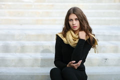 Closeup portrait of young beautiful brunette woman with wavy long hair stares into camera sitting on the concrete stairs Royalty Free Stock Images