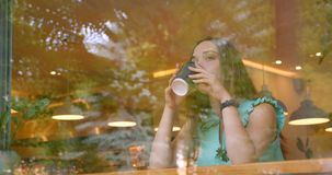 Closeup portrait of young beautiful caucasian female drinking coffee sitting in cafe indoors.  stock video footage