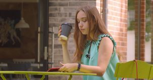 Closeup portrait of young beautiful caucasian female using phone and drinking coffee sitting in cafe outdoors.  stock video footage