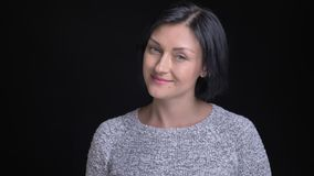 Closeup portrait of young beautiful caucasian woman with black hair smiling and nodding in token of agreement while. Looking straight at camera stock video footage