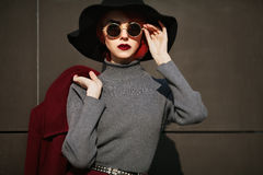 Closeup portrait of young beautiful fashionable woman with sunglasses. Lady posing on dark grey background. Model Royalty Free Stock Photos