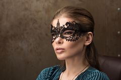 Closeup portrait of young beautiful lady in elegant masquerade mask. Black lace mask on the eyes. Professional makeup Stock Images